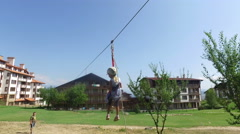 Child sliding on a zip line in mountain resort Stock Footage