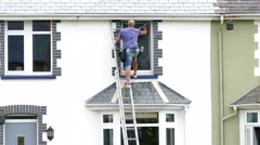 A window cleaner working up a ladder. Stock Footage