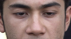 Sad and pensive eyes of a young adult man: mixed race asian Caucasian  Stock Footage