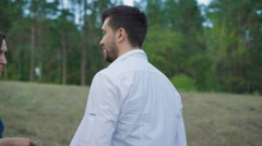 Romantic couple of young people are embracing a clearing in the summer forest Stock Footage