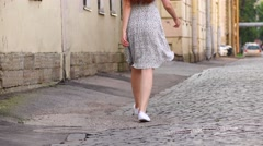 Young woman legs walk away block stone alley, light flying dress, old city Stock Footage