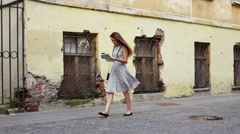 Tourist girl go in old downtown with map against shabby building, slow motion Stock Footage