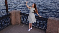 Young woman in light summer dress make selfie against blue waters, slow motion Stock Footage