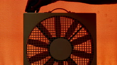 Silhouette of a man's hands connecting and turning on a fan. Stock Footage