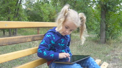 Pretty little girl with tablet computer sits on  bench in city park. Girl pla Stock Footage