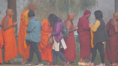 Monks lined up get offering from pilgrims early morning,Kushinagar,India Stock Footage