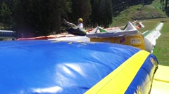 Summer tubing slide takes children down and jump at inflatable baloon bed Stock Footage