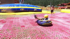Tourist enjoy having fun at summer Tubing Park in Bansko, Bulgaria Stock Footage