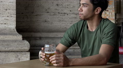 Pensive and nervous guy sips beer alone while thinking about his problems Stock Footage
