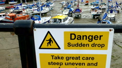 Sudden drop danger sign and moored boats in a harbour. Stock Footage