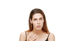 Displeased young beautiful girl listening, gesturing over white background. Slow Stock Footage