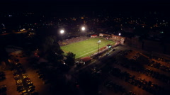 Slow aerial zoom to high school night football game Stock Footage