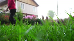 Woman with lawnmower in the backyard Stock Footage