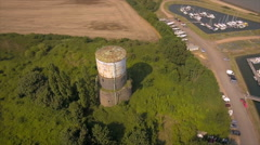 Old water tower in lush green bushes pan around. Aerial shot Stock Footage