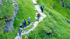 A group of elderly hikers walking up a hillside path in Cornwall. Stock Footage