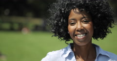 Young adult black woman in city park smile face portrait slow motion Stock Footage