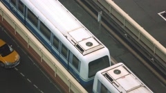 Aerial of An elevated train travels over a line of traffic during the day-Dan Stock Footage