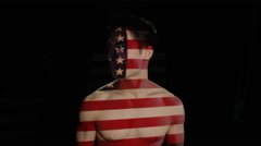 4K USA flag projected onto the face & body of male model on black background Stock Footage