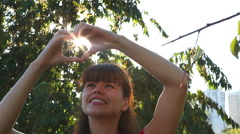 Adult woman showing heart with hands overhead in park as love concept Stock Footage