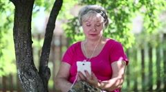 Senior woman sits on the chair in garden and communicates via smartphone Stock Footage