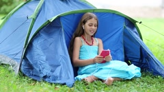 Beautiful girl sits on grass near tourist tent and communicates via smartphone Stock Footage