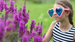 Beautiful girl in big glasses in the shape of hearts near purple flowers Stock Footage
