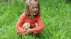 Little girl sits on green grass and crying Arkistovideo