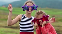 Cheerful girls in big glasses in the shape of stars looks at the camera Stock Footage