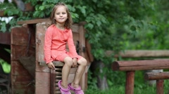 Funny little girl sits on the chair with spring Stock Footage
