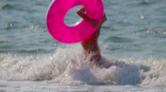 Woman walking in waves of beach on beautiful day unrekognizable people Stock Footage