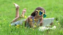 Beautiful girl in big sunglasses with tablet computer lies on the grass Stock Footage