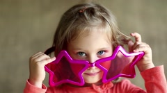 Pretty little girl in big glasses in the shape of stars looks at the camera Stock Footage