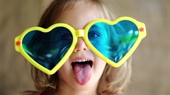Little girl in big sunglasses in the shape of hearts looks at the camera Stock Footage