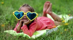 Beautiful little girl in big sunglasses lies on the grass Stock Footage