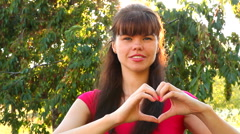 Girl shows heart with hands in park as love concept Stock Footage