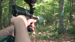 Slow Motion Paintball Gun Shooting Over The Shoulder Stock Footage