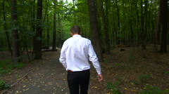 Young man in a white shirt walking on forest trail Stock Footage