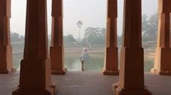 View through pillars to lake,BodhGaya,Mahabodhi Temple Complex,India Stock Footage