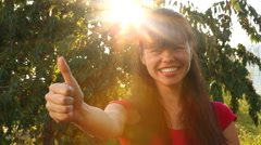 Young woman holding thumbs up or Like with copy space and sunshine on background Stock Footage