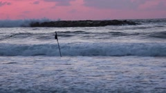 Dramatic waves in the sunset seen from shore, a man's silhouette walks through Stock Footage