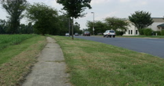 Vehicle Traffic Passing on Back Road with Walkway 10bit, 4K Stock Footage