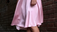 Woman in pink dress with billowing skirt, stands near the brick wall Stock Footage