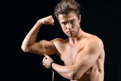 Strong sportsman measuring his bicep Stock Photos