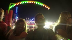 Slowmotion of happy people enjoying roller coaster ride in amusement park at nig Arkistovideo