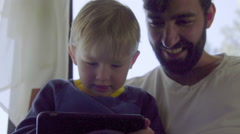 Father and boy wathc movie on mobile phone Stock Footage