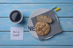 Inexpensive bun, a cup of coffee and two slices of sugar on a blue wooden table. Stock Photos