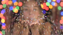 A happy attractive woman blows confetti at the camera in slow mo Stock Footage
