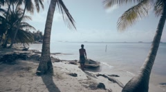 Fishermen contemplating caribbean beach Stock Footage