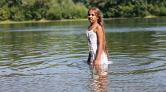 Girl in a white dress standing in the river Stock Footage