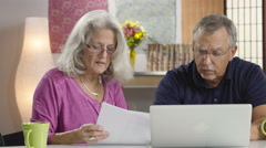 Senior aged couple looking at their bills Stock Footage